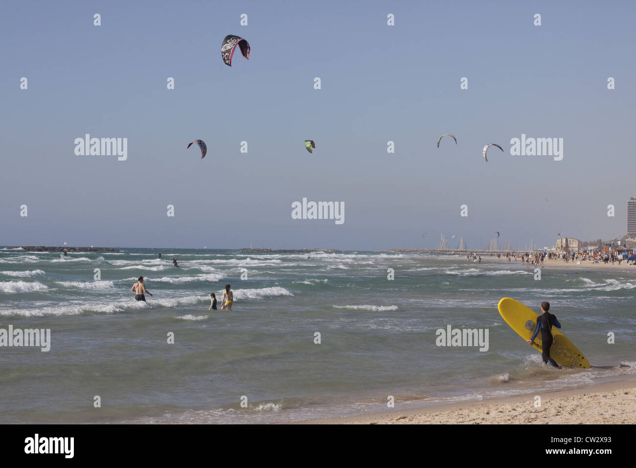 Surfer entrata in acqua con kite-surf e nuotatori in background, Tel Aviv, Israele Immagini Stock