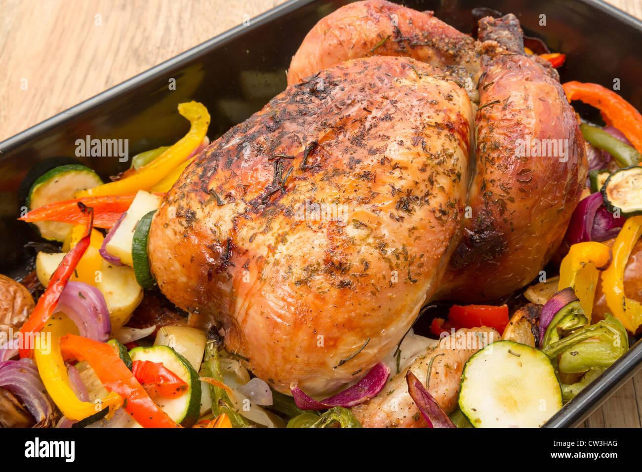 Un pronto a mangiare fresco di pollo arrosto in una teglia da forno con verdure arrosto - studio shot Immagini Stock