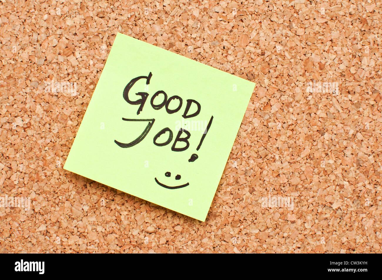 Bigliettino giallo su un ufficio cork bulletin board con buon lavoro - motivare nota. Immagini Stock
