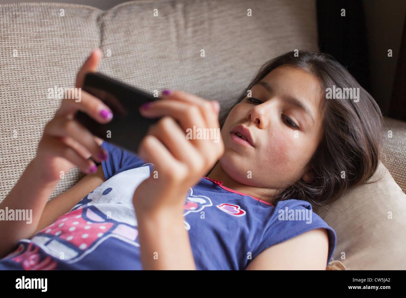 Giovane ragazza riproduce su telefono cellulare a casa Immagini Stock