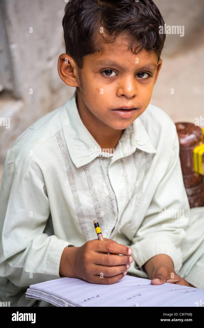 Giovane ragazzo pakistano scrivere in inglese in tale pur Village, Islamabad, Pakistan Immagini Stock
