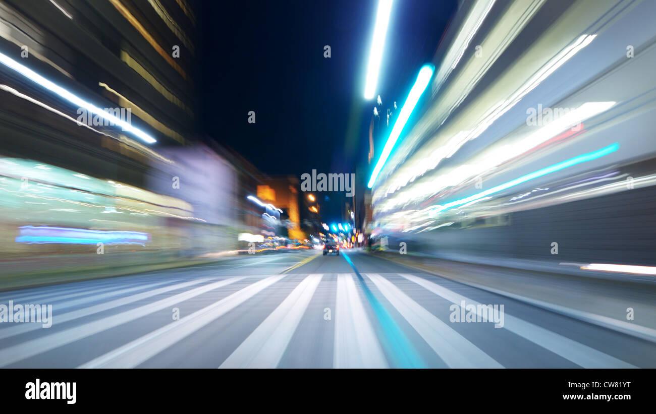 Moto vista offuscata di guidare di notte attraverso la città Immagini Stock