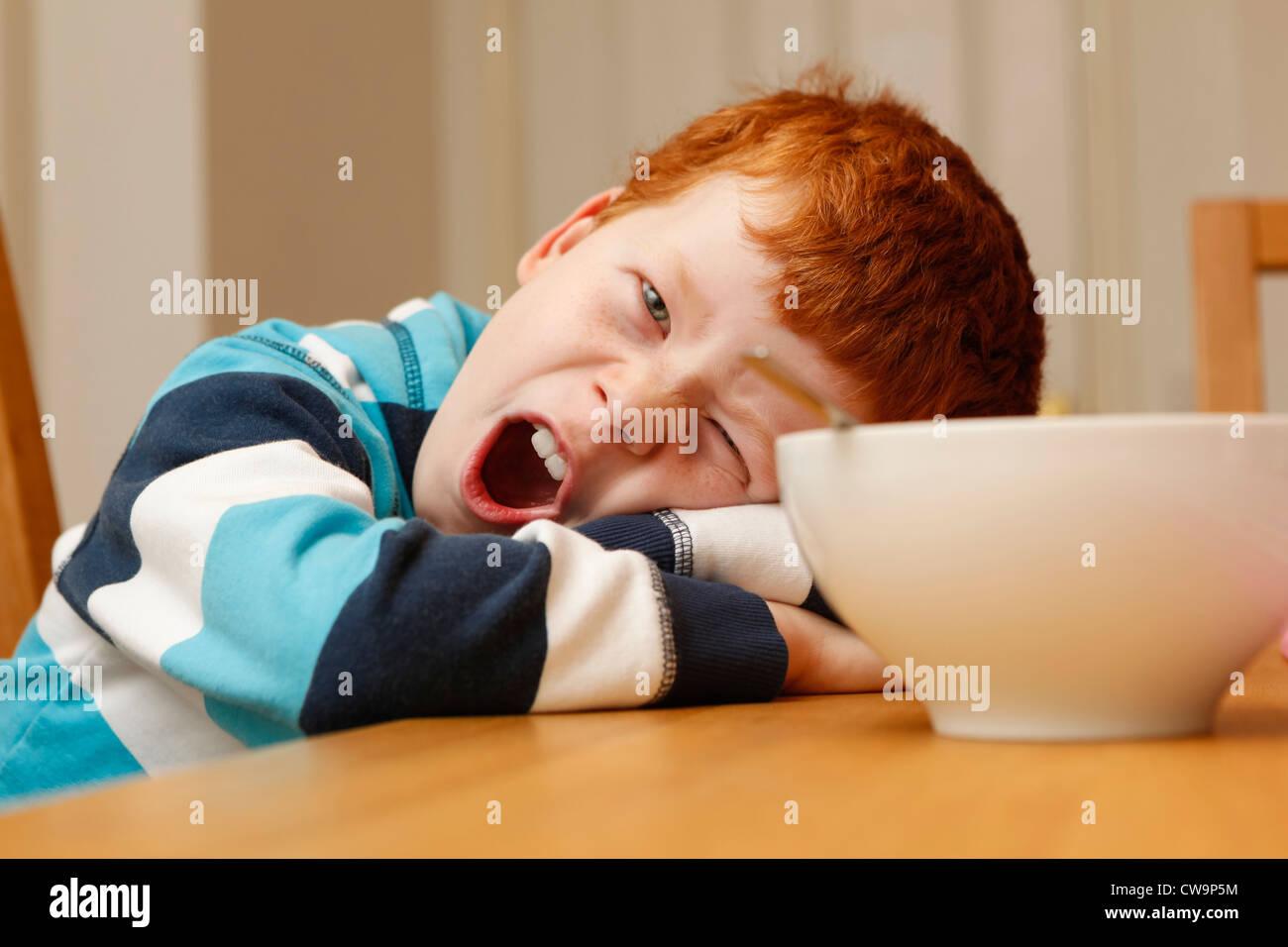 8 anno vecchio ragazzo stanco al tavolo della colazione Immagini Stock