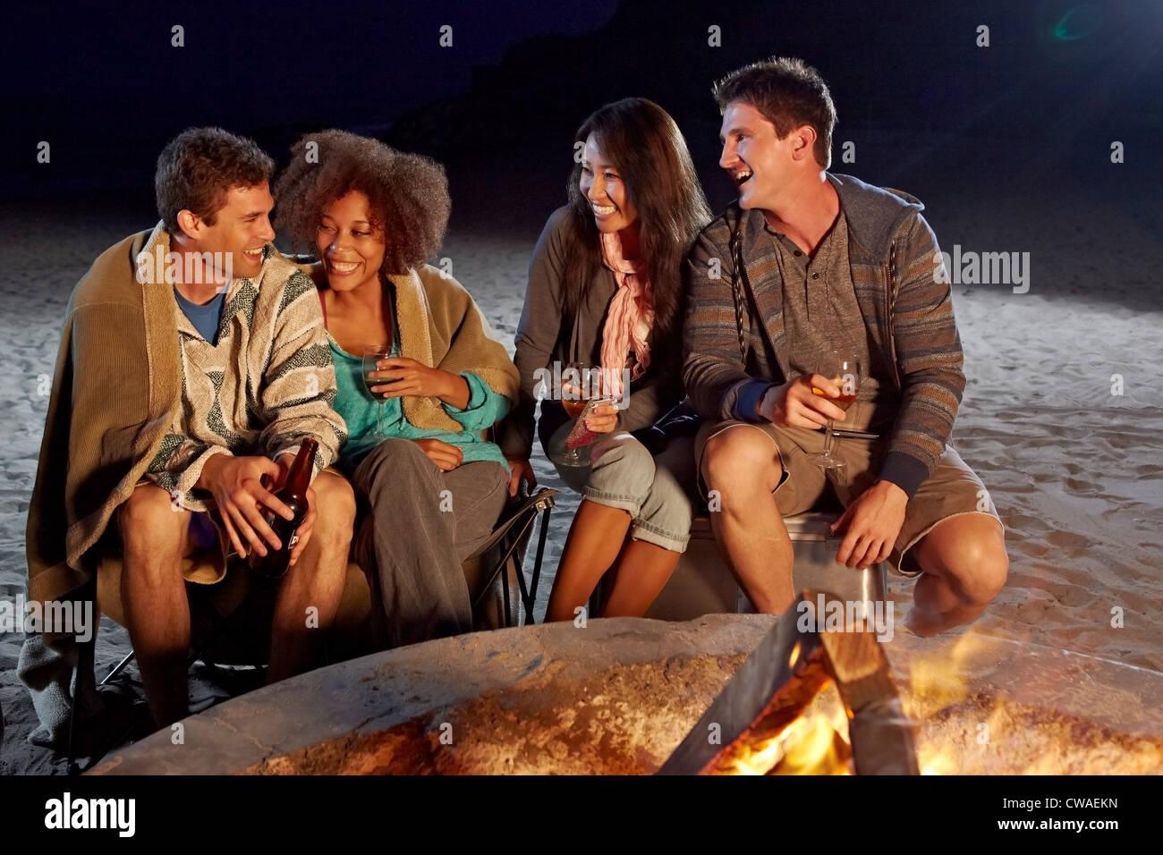 Amici avente una festa sulla spiaggia di notte Immagini Stock