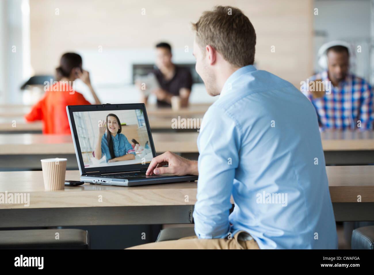 Giovane uomo utilizzando notebook per avere la chiamata video con la fidanzata Immagini Stock
