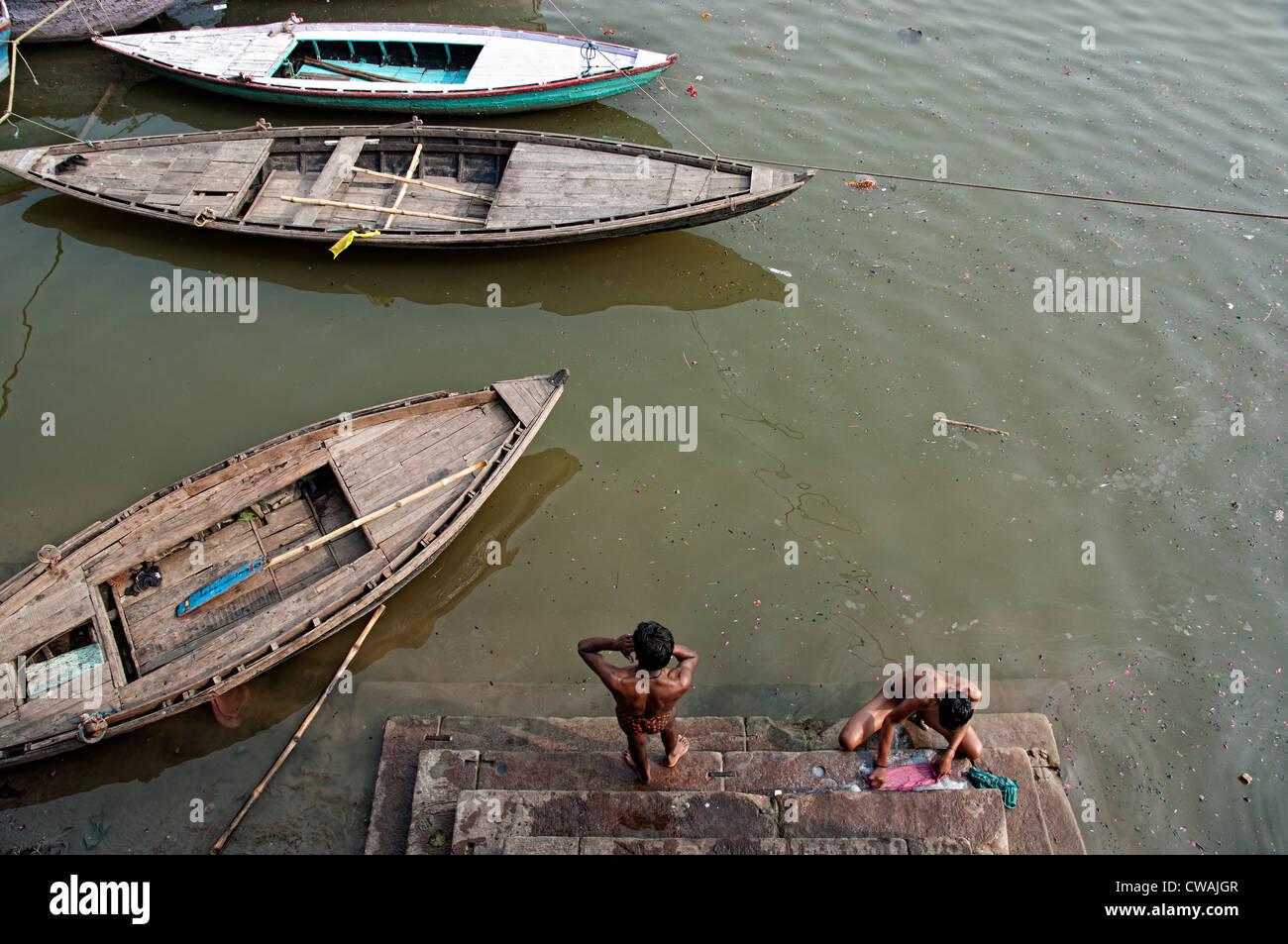 Giovani uomini la balneazione e di lavaggio nel ghats del fiume Gange. Varanasi, India Foto Stock