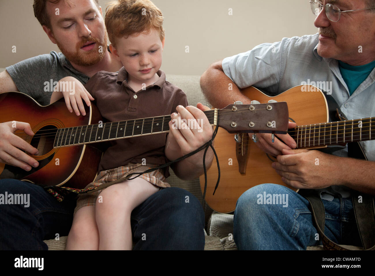 Padre figlio di insegnare a suonare la chitarra, con il nonno Immagini Stock