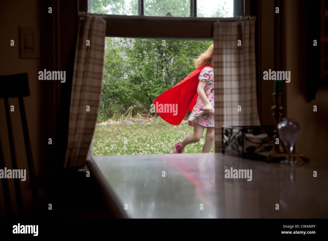 La ragazza di un capo in esecuzione passato una finestra aperta Immagini Stock