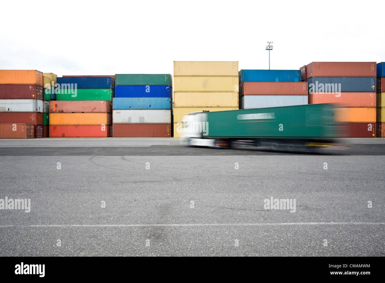 I carrelli guida tra i contenitori di spedizione Immagini Stock