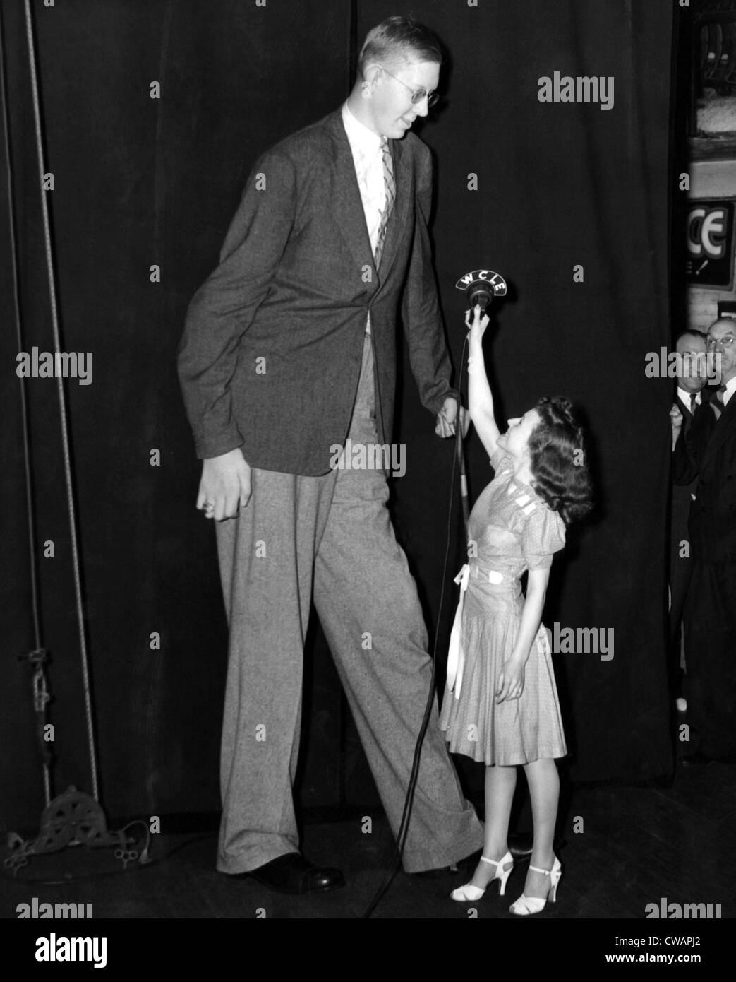 Robert Wadlow, più alte del mondo, l'uomo con la signorina Angela Rizzo, 19. ca.1940.. La cortesia: CSU Immagini Stock