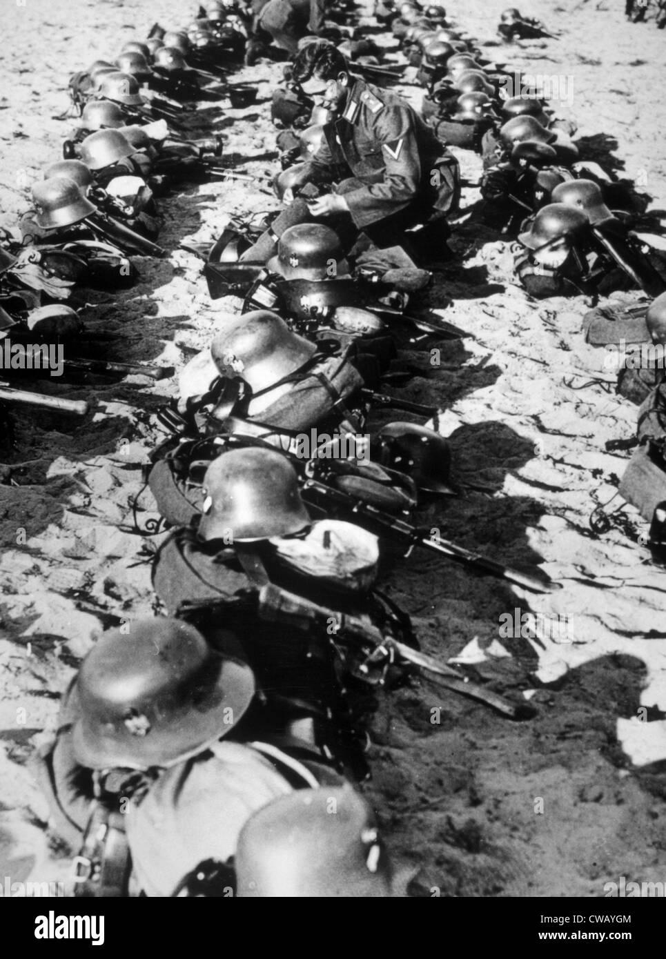 La Germania nazista, un soldato tedesco ispezione elmetti di acciaio e di altre attrezzature per la Wehrmacht (forze Immagini Stock