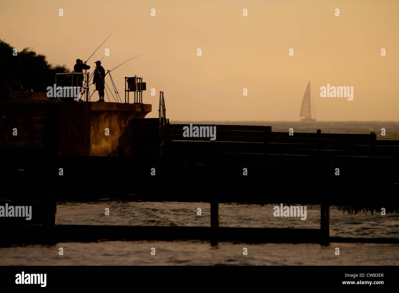Pesca sportiva, pesca, pescatori, Seawall, pennelli, yacht, nebbia, Colwell Bay, Isle of Wight, England, Regno Unito Immagini Stock