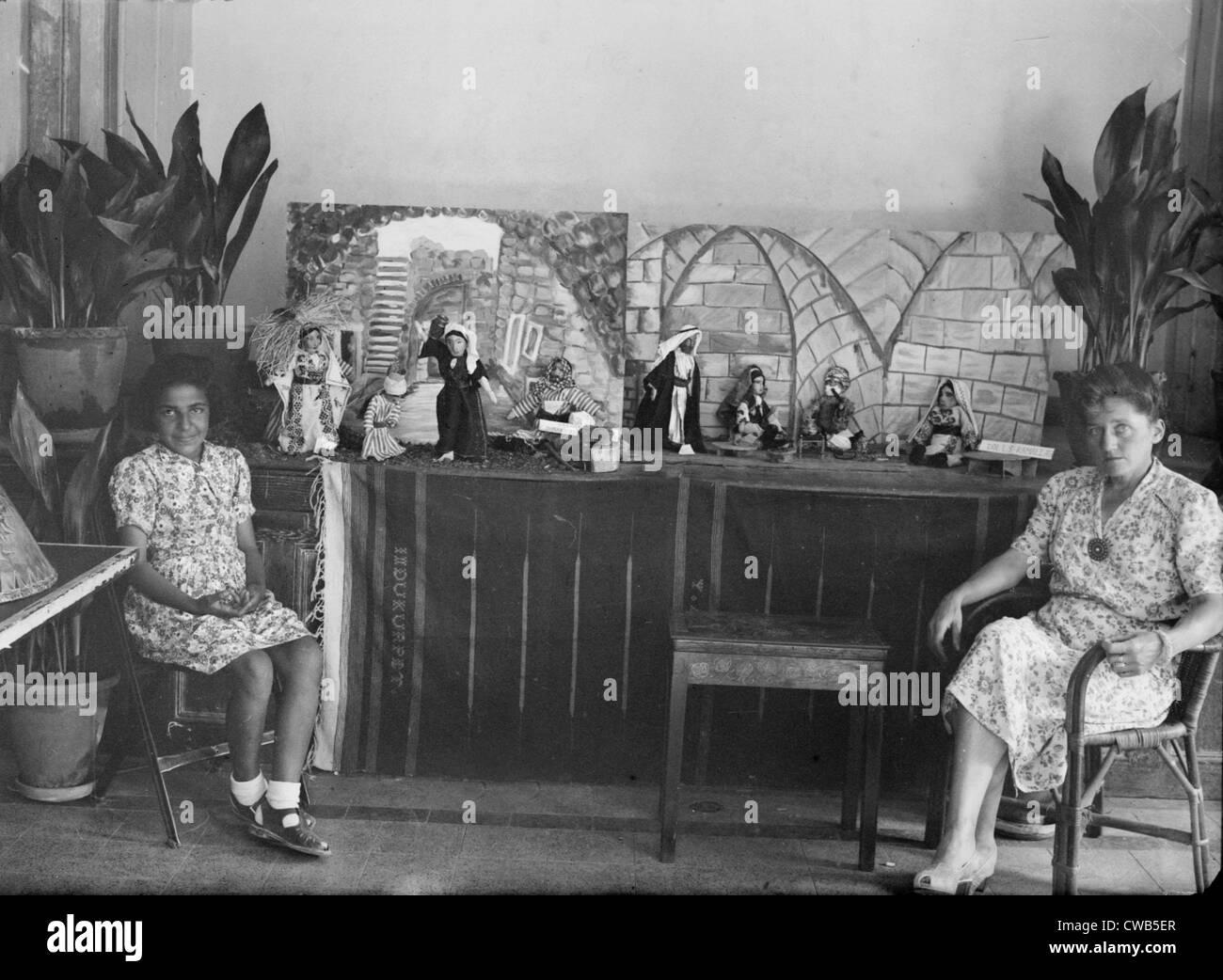 07217e892863 Donna e bambina seduti davanti di bambole che sono indossando il tradizionale  abito Arabo