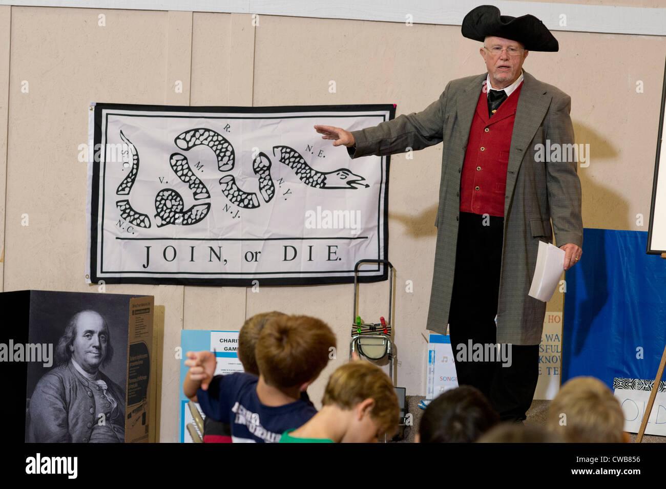 """Costume volontario utilizza poster di American padre fondatore Ben Franklin's """"unirsi o morire"""" cartoon Immagini Stock"""