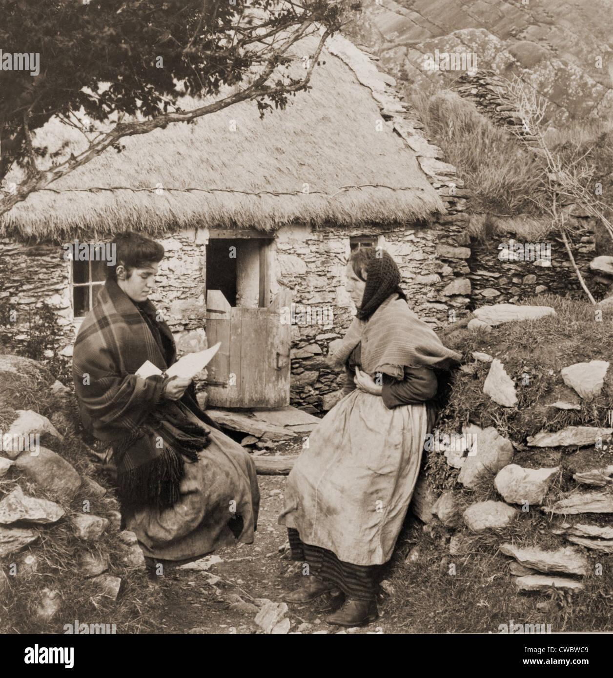 Una lettera da PAT IN AMERICA. Giovane donna irlandese la lettura di una lettera da un parente in America per una Immagini Stock
