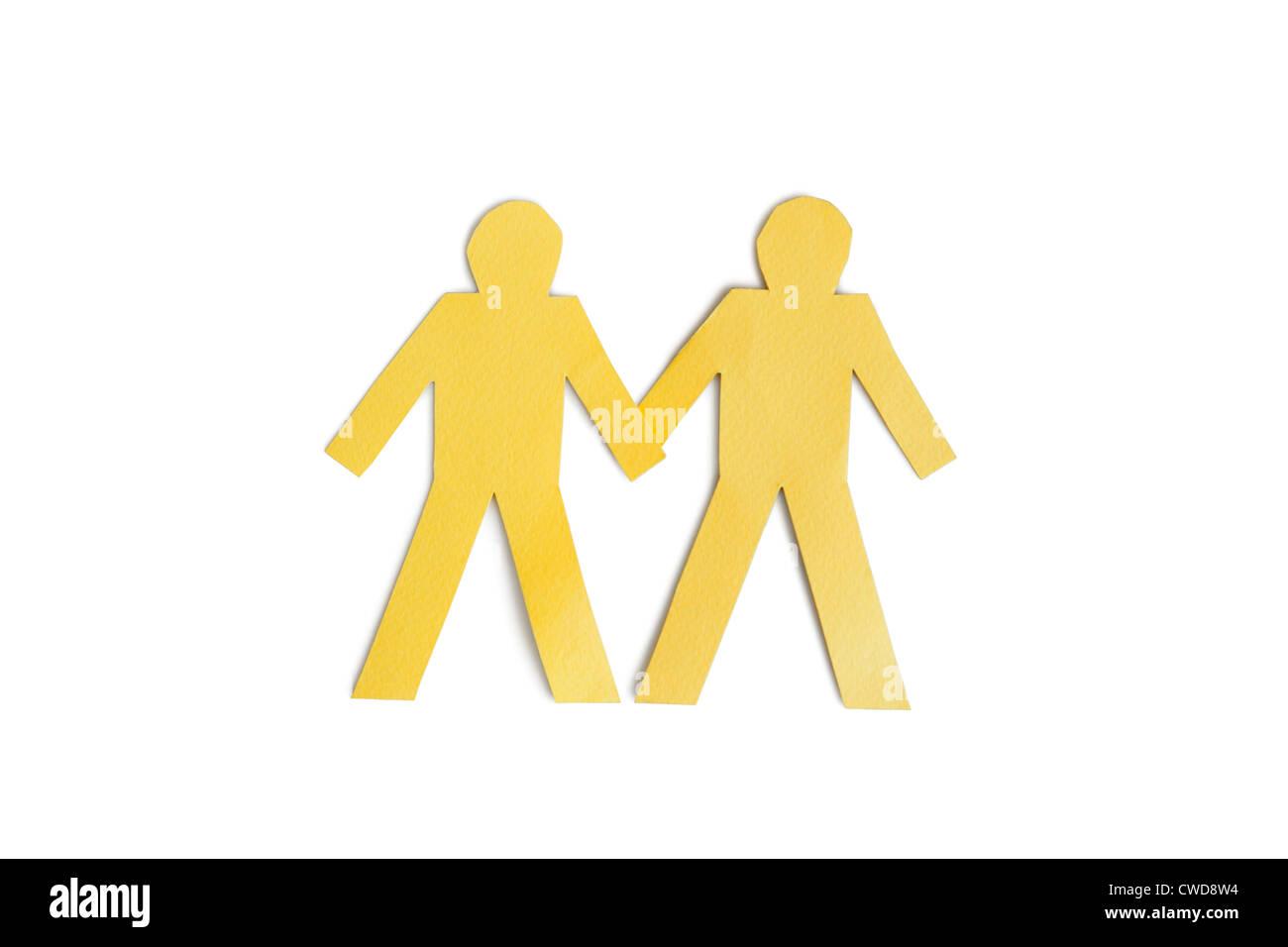 Due carta gialla ritagliare figure tenendo le mani su sfondo bianco Foto Stock