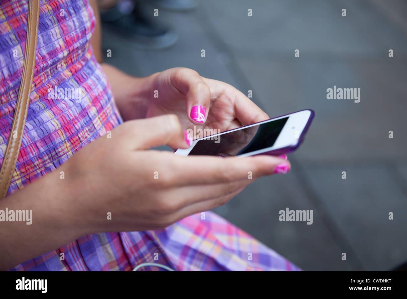 Ragazza giovane,con unghie verniciate invia messaggio sul touch screen smart phone-close-up Foto Stock