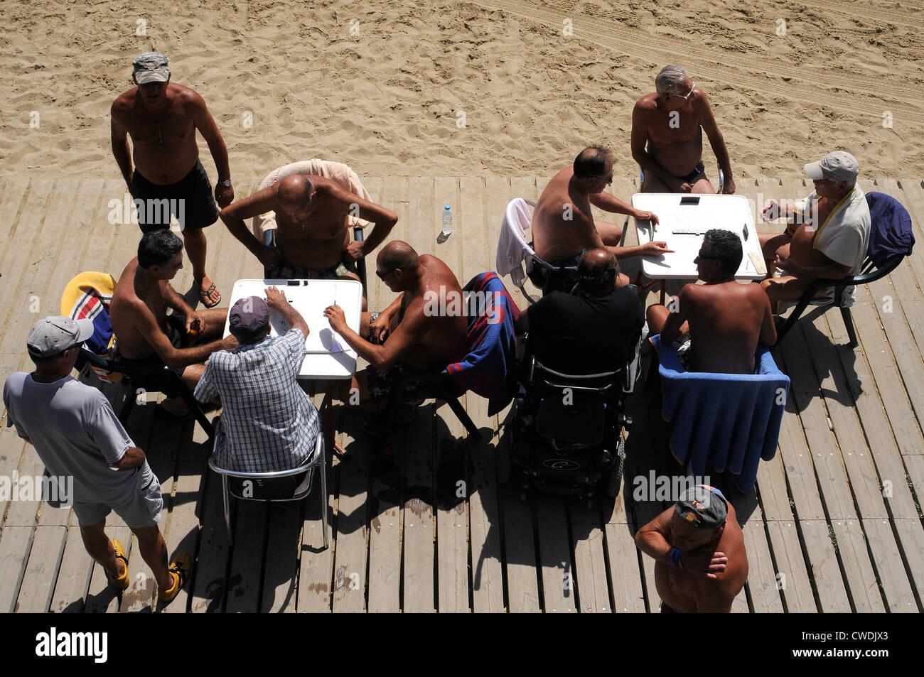 Gli uomini la riproduzione di domino sul lungomare di Barceloneta, Barcellona Immagini Stock