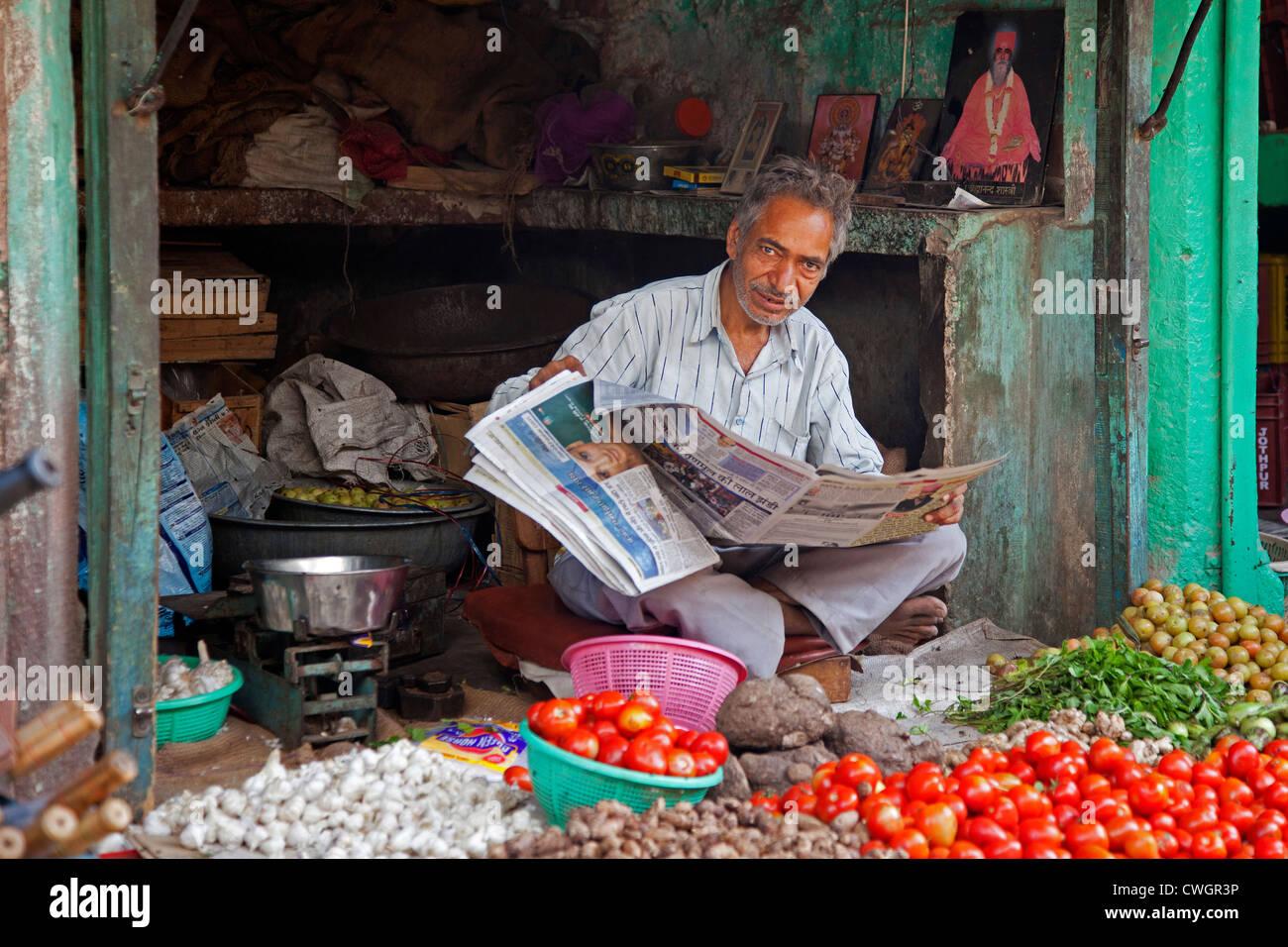 Negoziante leggendo il giornale in negozio di alimentari vendita di verdure a Jodhpur, Rajasthan, India Immagini Stock