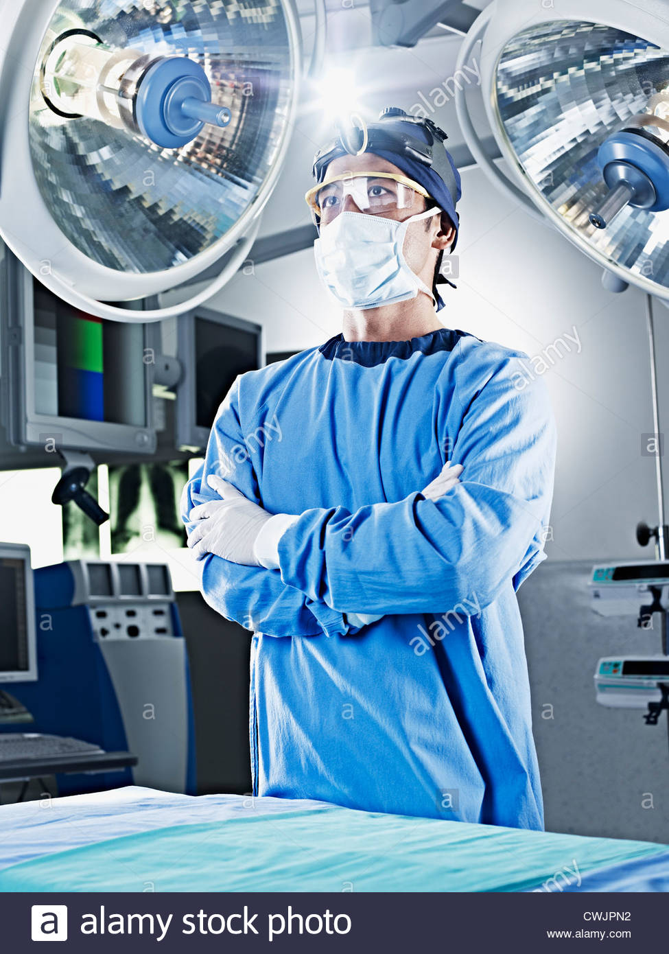 Ritratto di chirurgo serio con le braccia incrociate sotto le luci chirurgico Immagini Stock