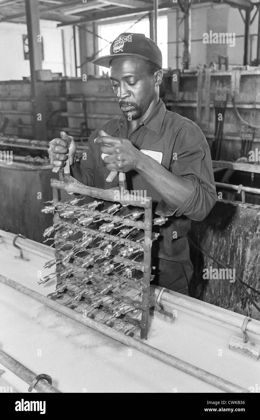 Un uomo, blu collare lavoratore, lavorando con le proprie mani in una fabbrica. Immagini Stock