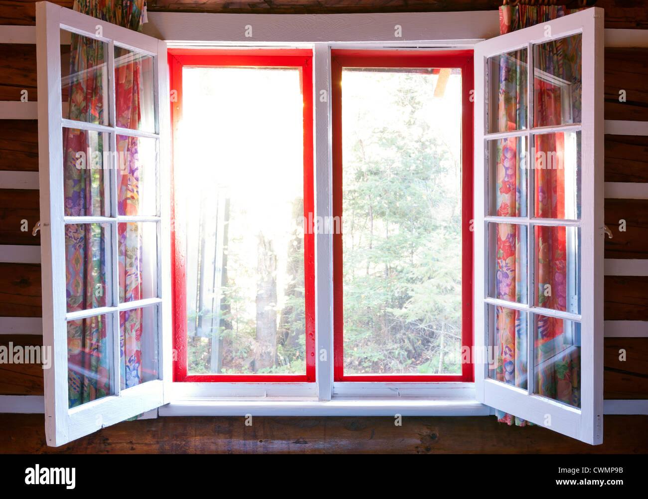 Aprire windows in cottage con sole e vista della foresta Immagini Stock