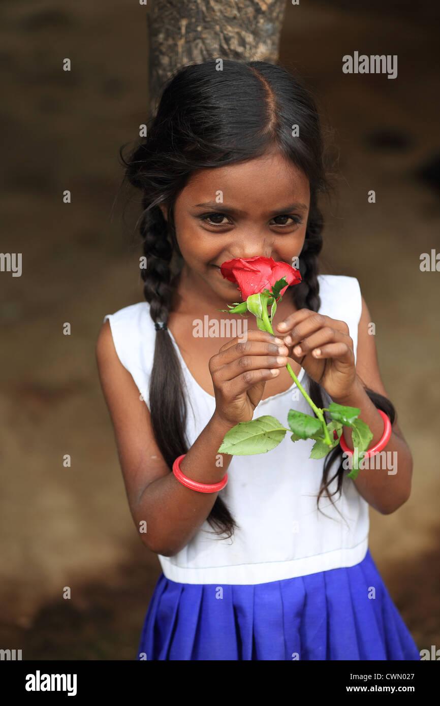 Giovani indiani ragazza rurali tenendo una rosa di Andhra Pradesh in India del Sud Immagini Stock