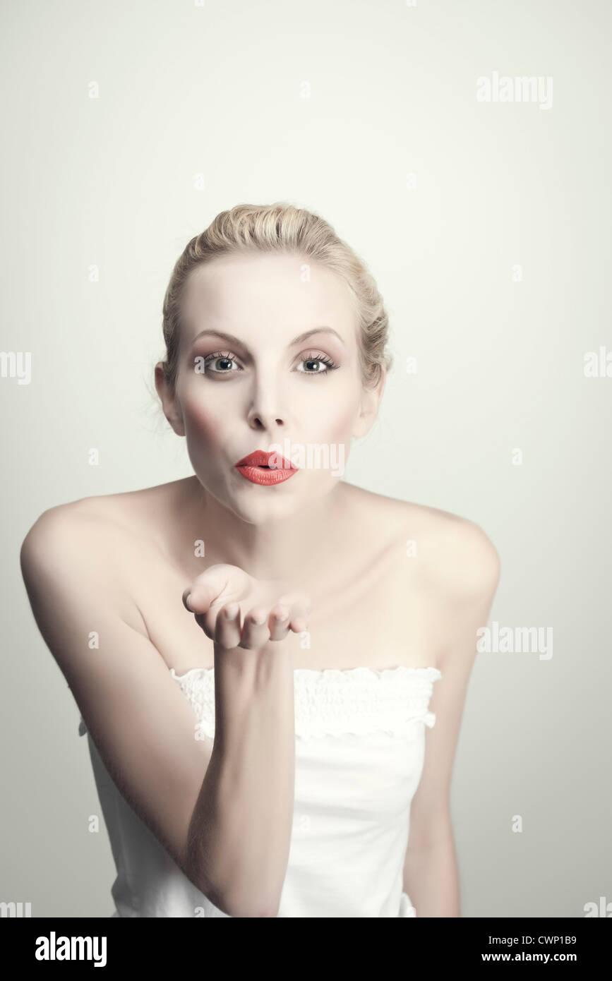Giovane donna soffiando kiss, ritratto Immagini Stock