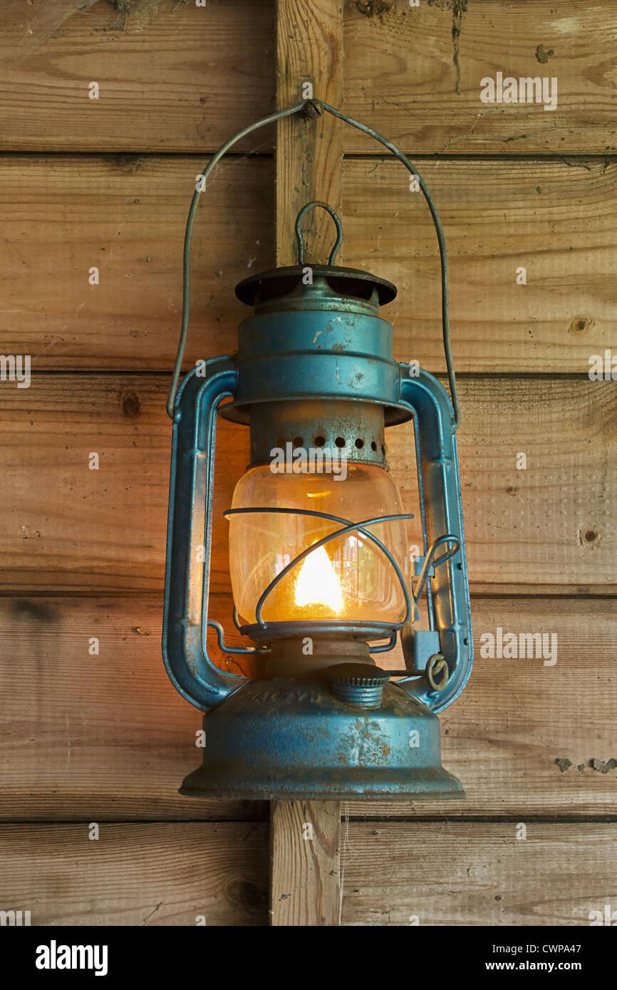 Rusty lit lanterna blu appesa in un vecchio capannone Immagini Stock
