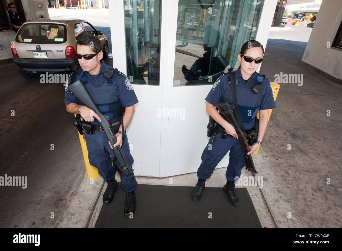 Maschio e femmina, ufficiali di guardia con pistole a Laredo, Texas ponte internazionale. Immagini Stock