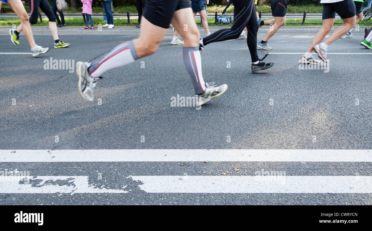 Le persone che eseguono velocemente in una maratona della città sulla strada Immagini Stock