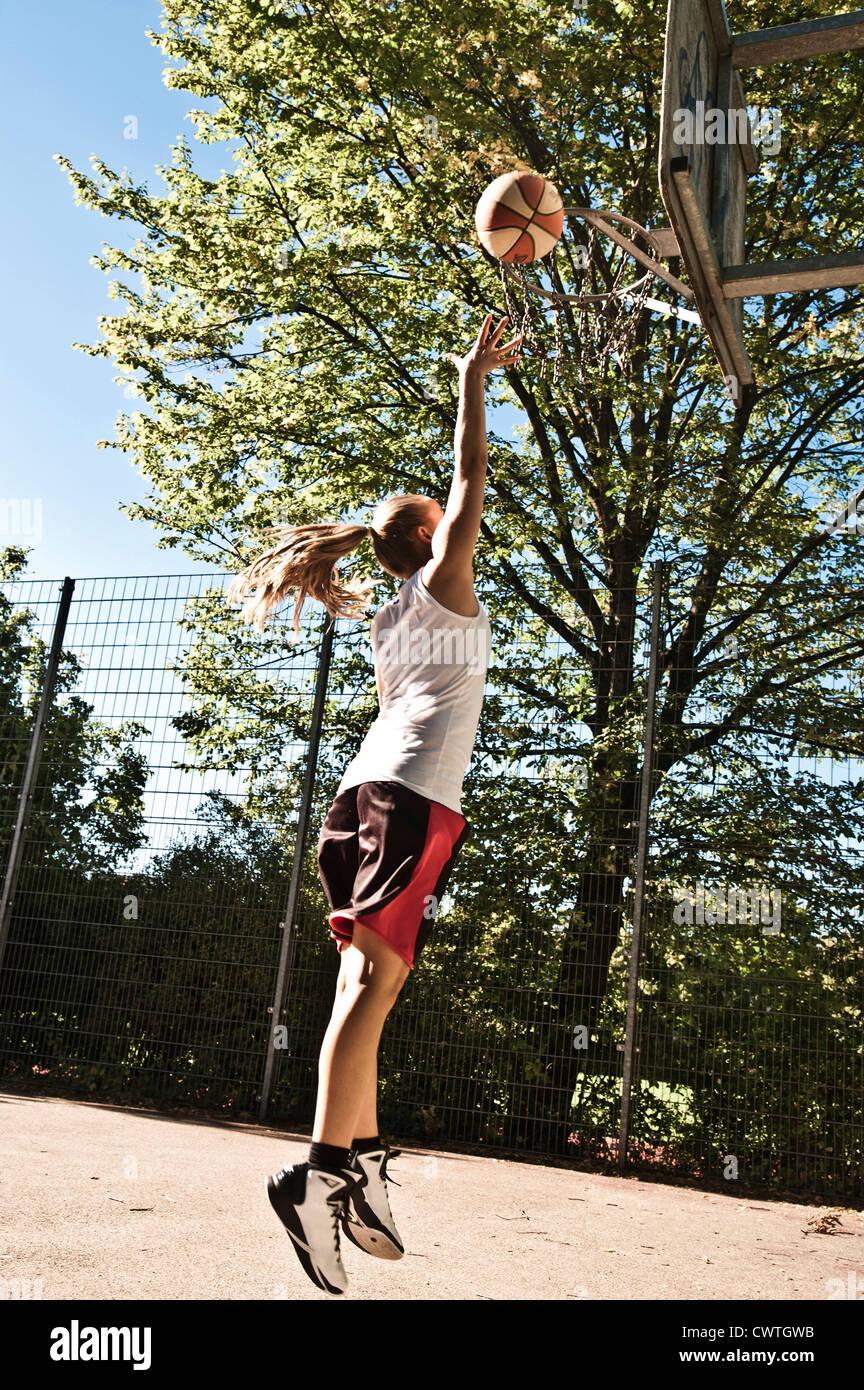 Ragazza adolescente giocare a basket Immagini Stock