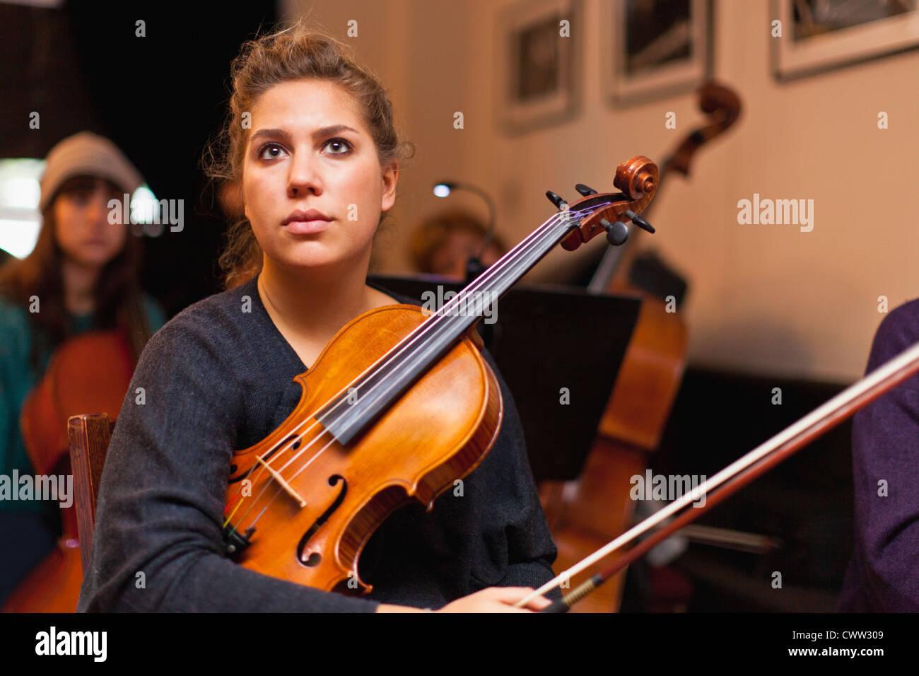 Violino giocatore seduto in pratica Immagini Stock