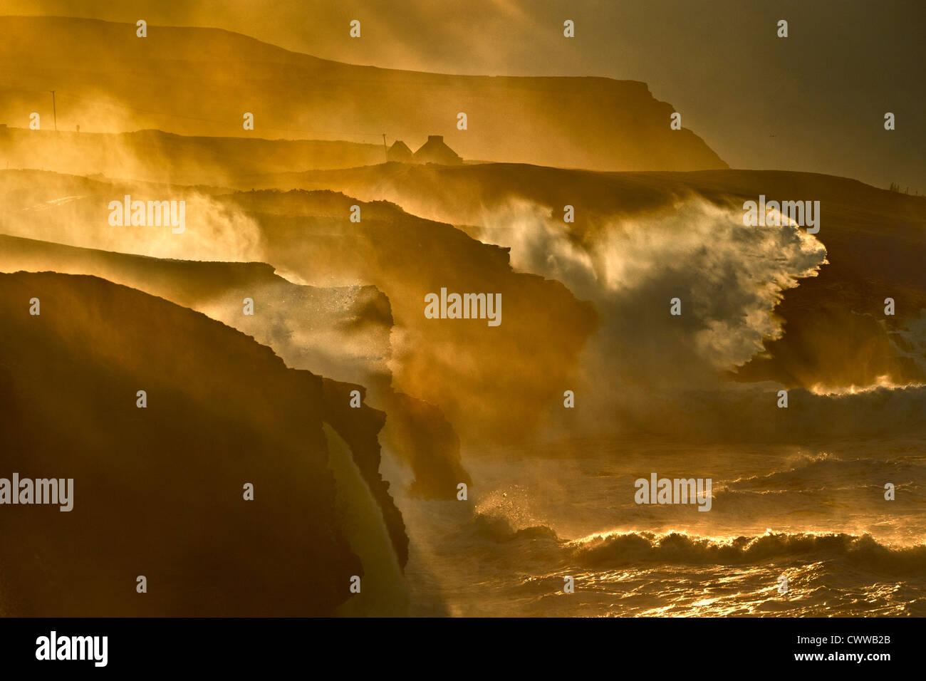 Le onde che si infrangono sulle scogliere rocciose Immagini Stock