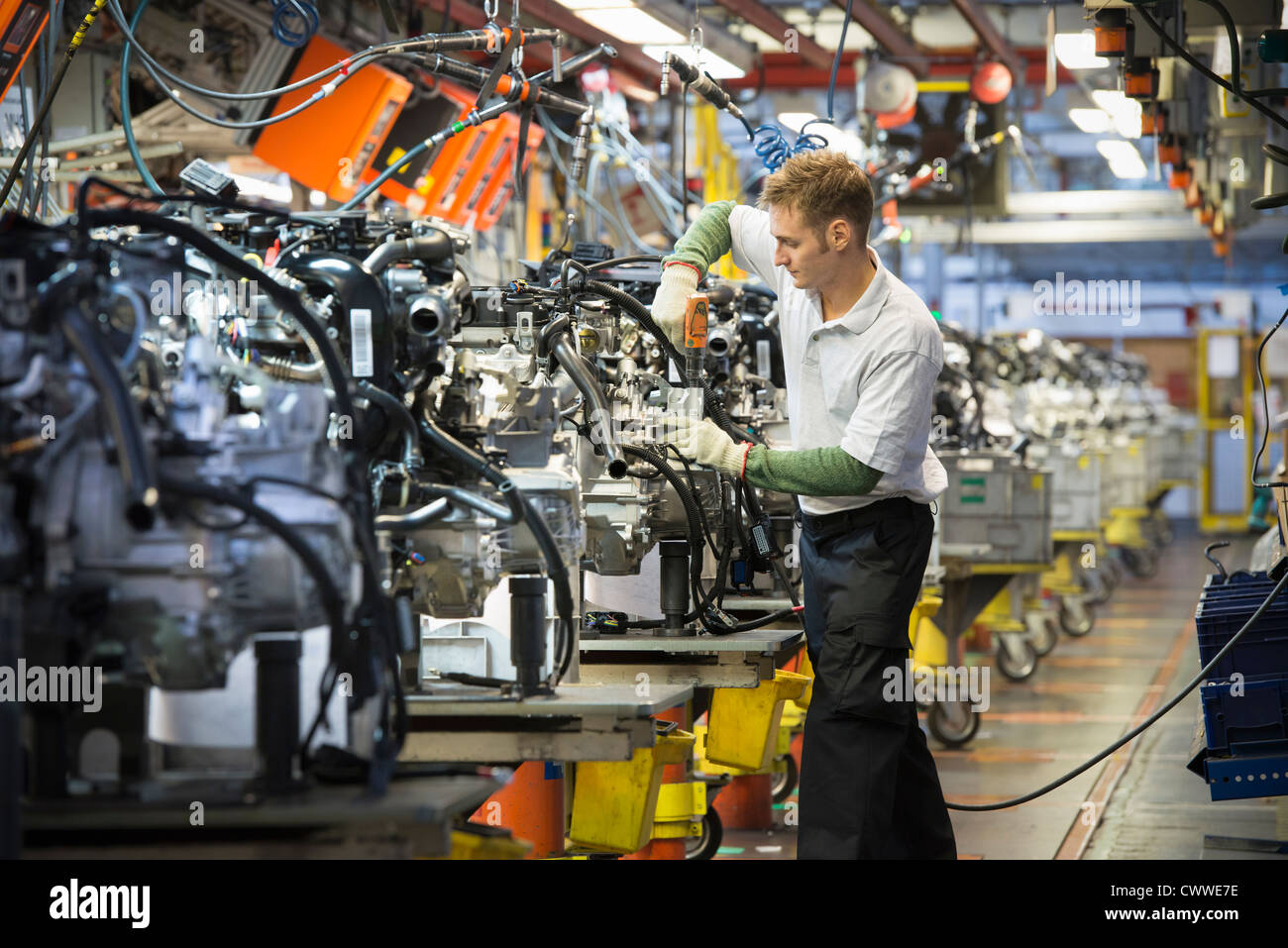 Lavoratore con motori su linea di produzione nella fabbrica di automobili Immagini Stock