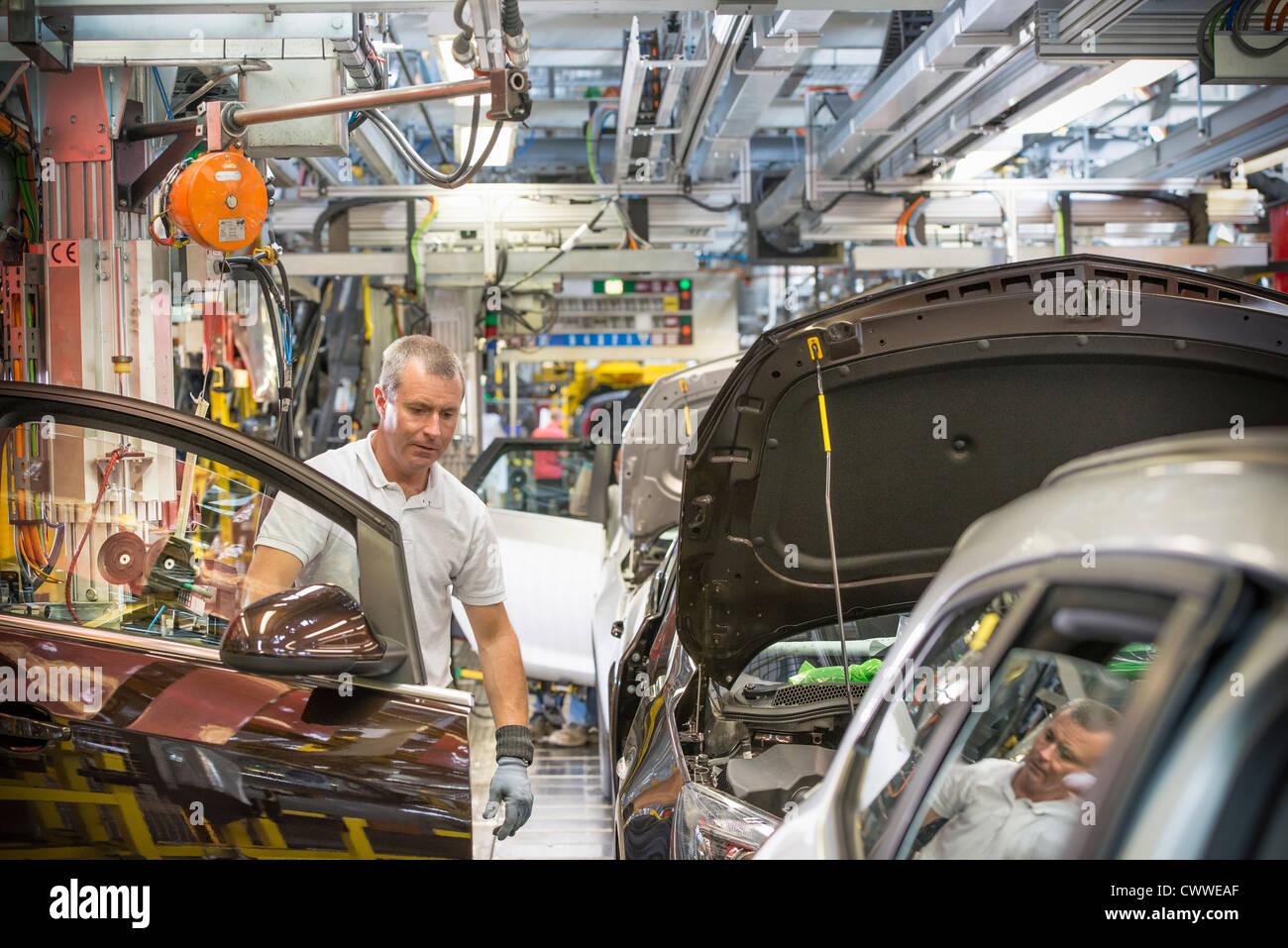 Lavoratore montaggio di porte in auto nella fabbrica di automobili Immagini Stock