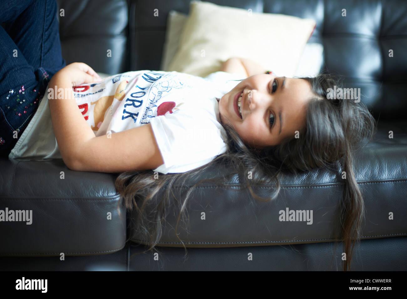 Sorridente ragazza rilassante sul divano Immagini Stock