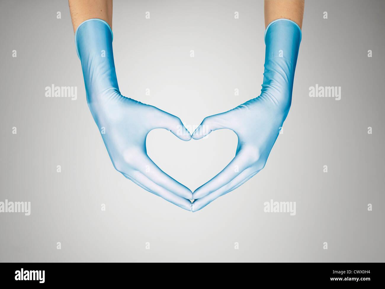 Mani guantate messa a forma di cuore Foto Stock