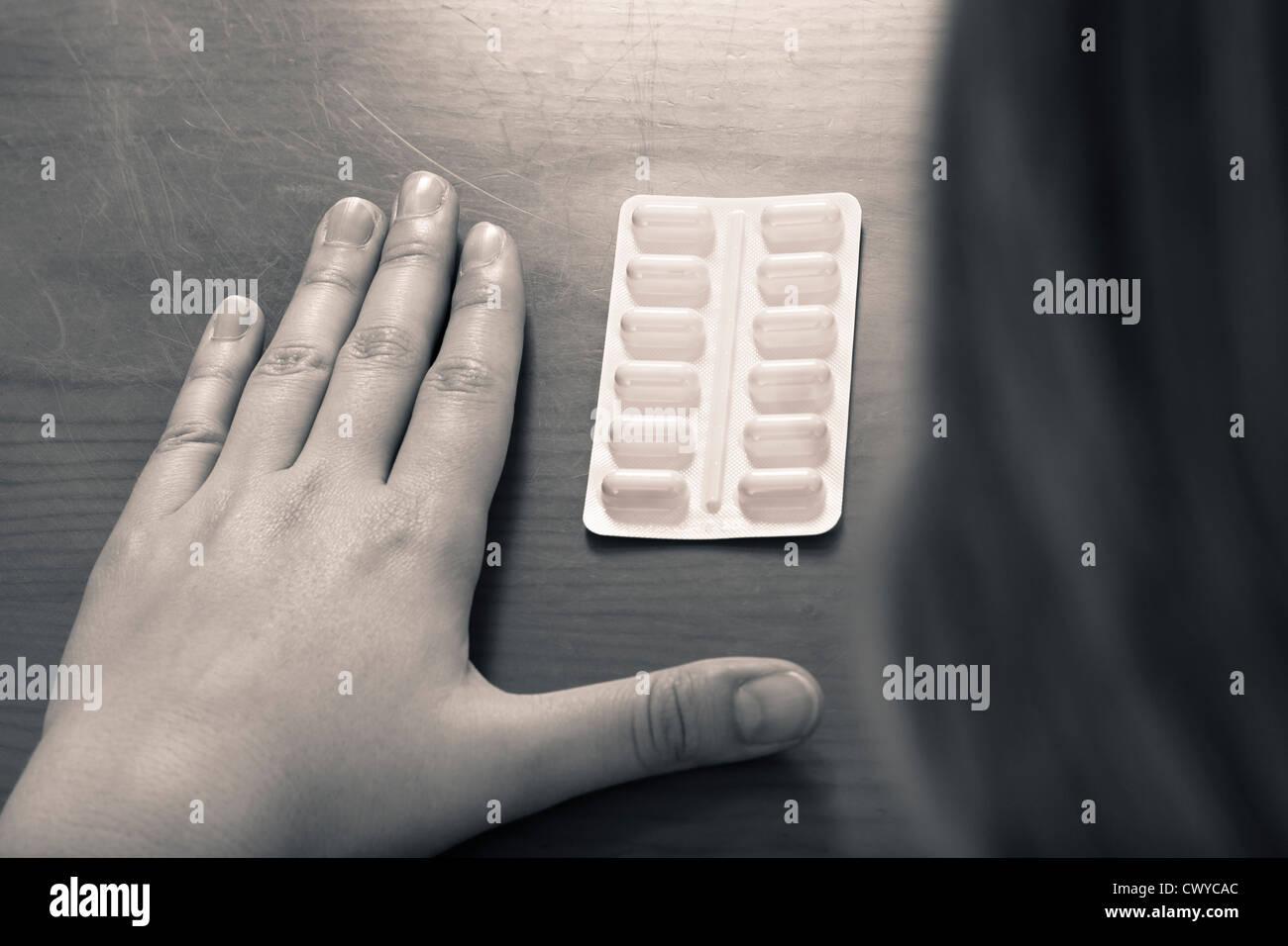 Foto drammatica della mano femminile e pillole, medicina tossicodipendenze concetto. Immagini Stock