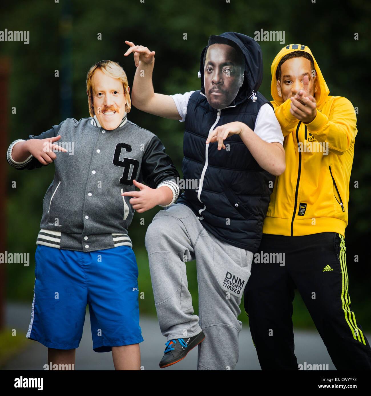 Tre ragazzi adolescenti indossando 'celebrità' maschere - Keith Lennon, Will Smith e.I.am, REGNO UNITO Immagini Stock