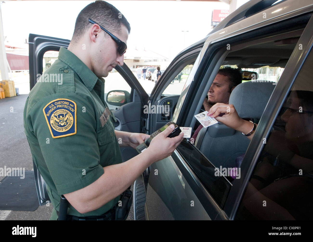 Ufficiali con il servizio doganale statunitense e la Pattuglia di Confine ispezionare vetture voce dal Texas in Immagini Stock