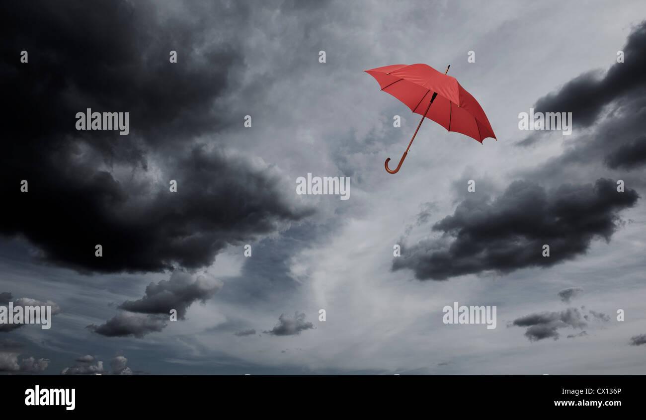 Ombrellone rosso galleggiante attraverso cielo molto nuvoloso Immagini Stock