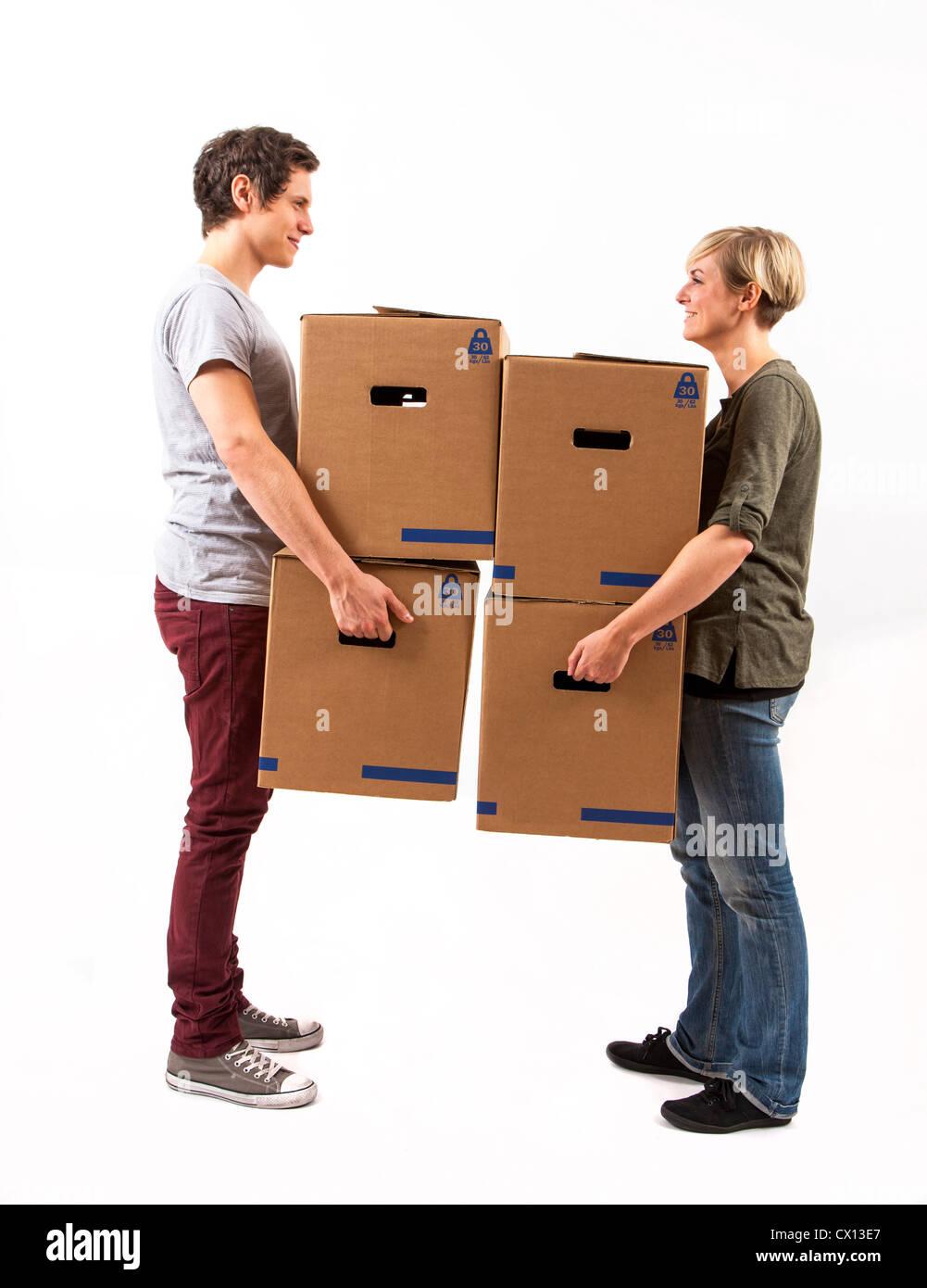 Symbolfoto Umzug, Auszug, umziehen. Junges Paar trägt Umzugskartons. Umzugskisten Pappkarton aus. Foto Stock