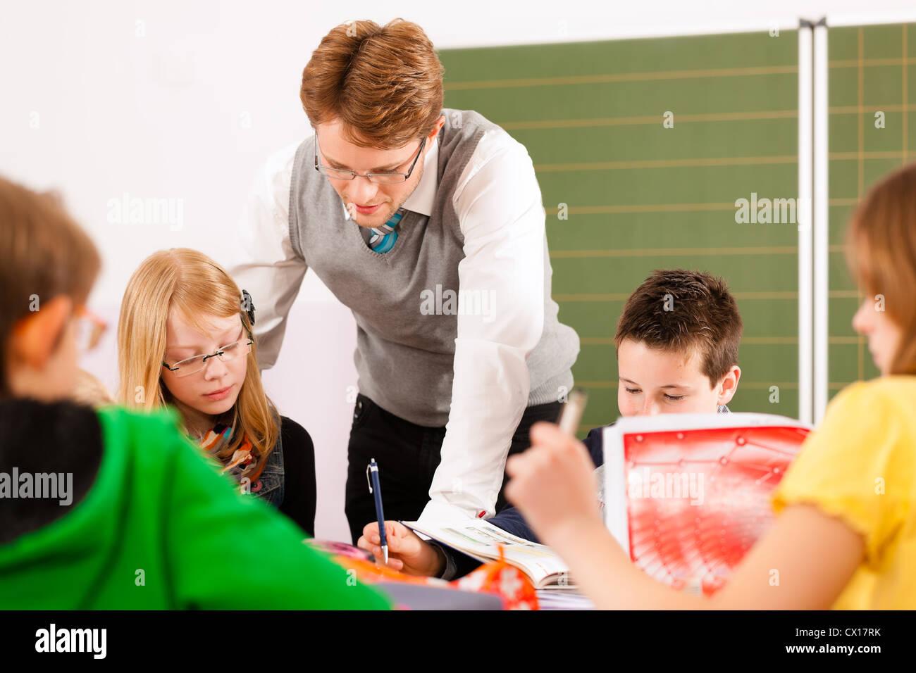 Istruzione - Studenti e insegnanti apprendimento presso la scuola elementare o per la scuola primaria in classe Immagini Stock
