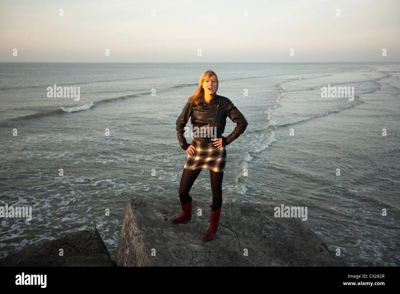 Ragazza bionda flirtare al tramonto vicino al mare Foto Stock