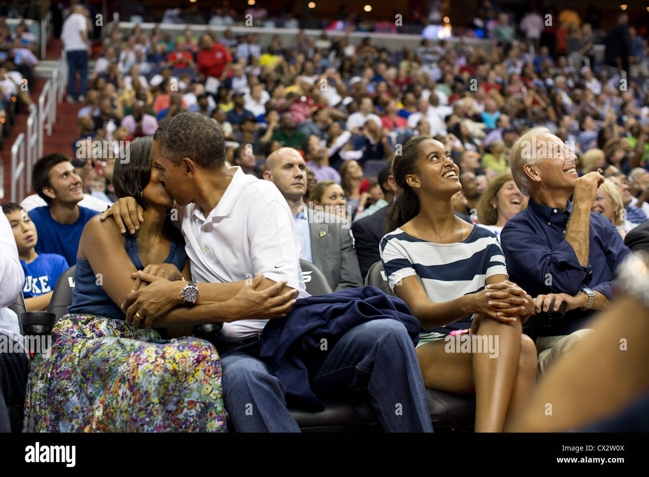 """Il presidente Barack Obama bacia la First Lady Michelle Obama per il """"Kiss Cam' mentre frequentano uomini Immagini Stock"""