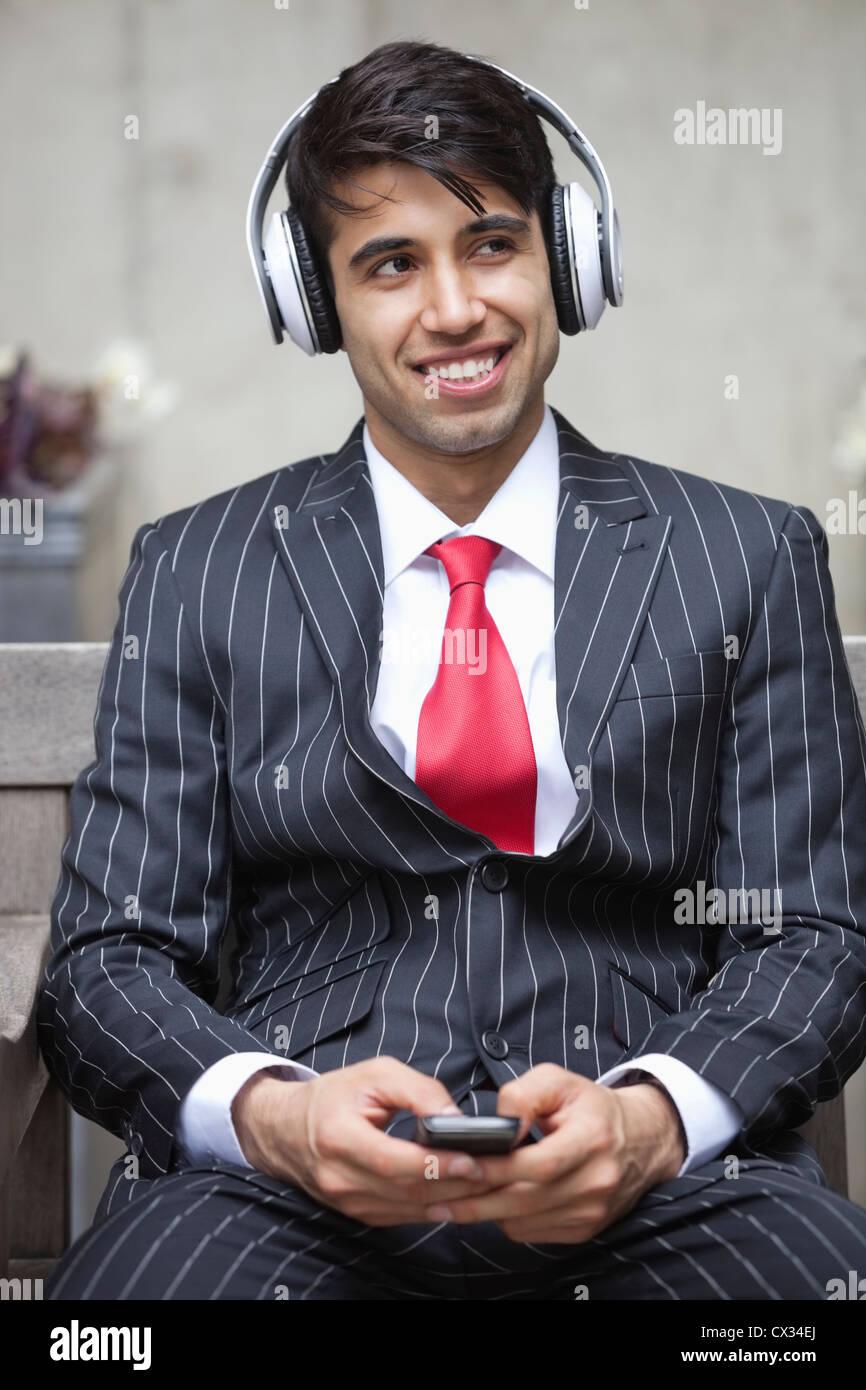 Giovane imprenditore indiano ascoltando musica sulle cuffie Immagini Stock
