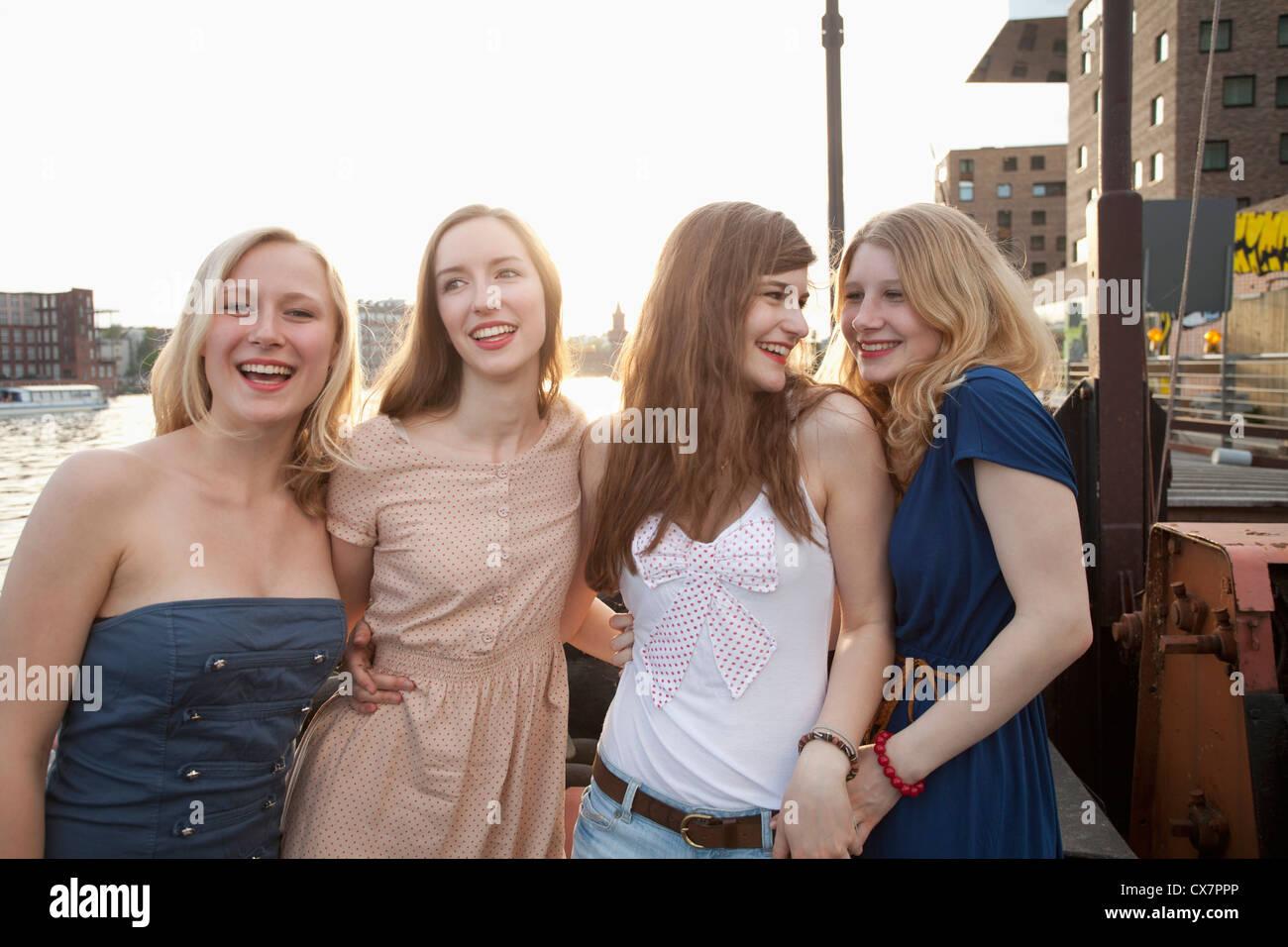 Quattro amiche in piedi a fianco a fianco, il fiume Sprea, Berlino, Germania Immagini Stock