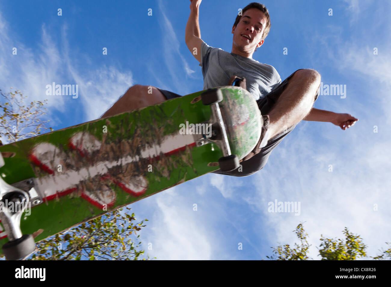 Giovane uomo saltando su uno skateboard - USA Immagini Stock