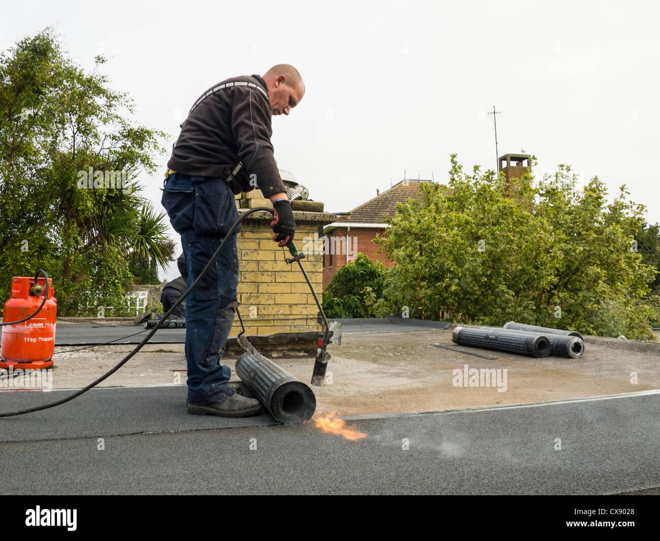 Un operaio che stabilisce una torcia di feltro sul rivestimento del tetto su un tetto piatto. Immagini Stock
